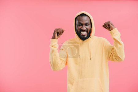 laughing african american man with raised arms isolated on pink background
