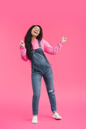 attractive stylish young african american woman dancing on pink background