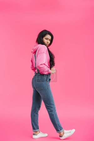 stylish young african american woman in denim overall posing on pink background