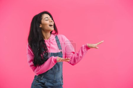 happy african american woman with closed eyes dancing isolated on pink background