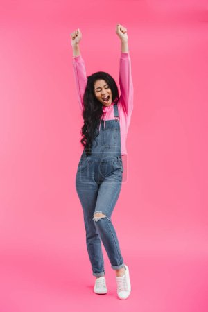 excited stylish young african american woman in denim overall with raised arms on pink background