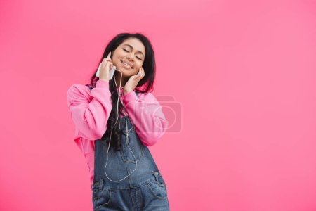 attractive african american woman with closed eyes in earphones listening music with smartphone isolated on pink background