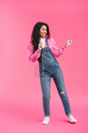 smiling african american woman in earphones listening music with smartphone dancing on pink background