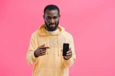 young african american man in earphones pointing at  smartphone with blank screen isolated on pink background