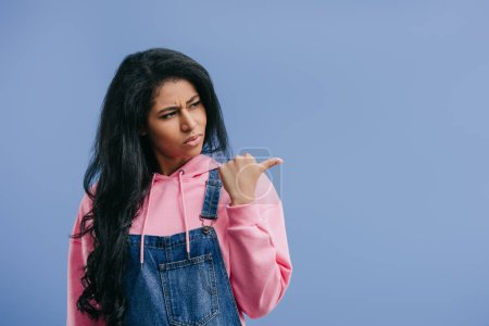angry young african american woman pointing aside isolated on blue background