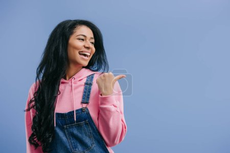 smiling young african american woman pointing aside by finger isolated on blue background