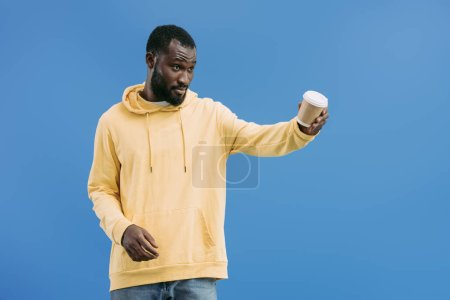 young african american man offering disposable coffee cup isolated on blue background
