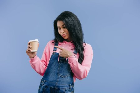 african american woman pointing at disposable coffee cup isolated on blue background