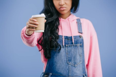 partial view of young african american woman showing disposable coffee cup isolated on blue background