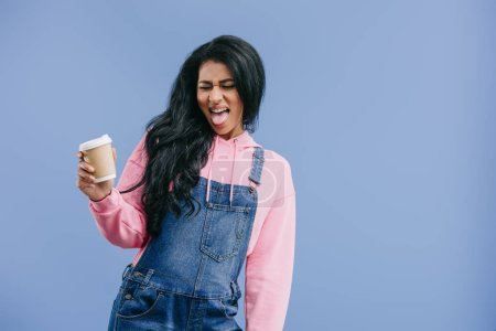 disappointed african american woman with grimace on face holding disposable coffee cup isolated on blue background