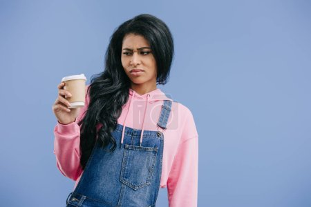 upset young african american woman with disposable coffee cup isolated on blue background