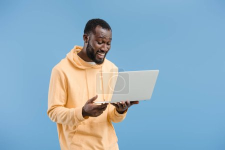 happy young african american man with closed eyes holding laptop isolated on blue background