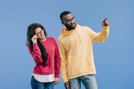 serious african american man pointing by finger to shocked girlfriend adjusting eyeglasses isolated on blue background