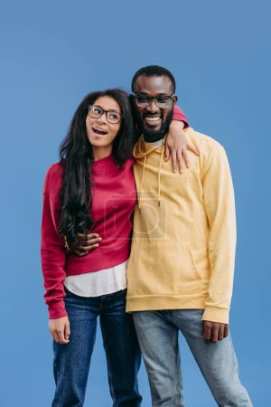 stylish happy african american couple in eyeglasses embracing each other isolated on blue background