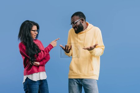 angry african american woman pointing by finger at boyfriend doing shrug gesture isolated on blue background