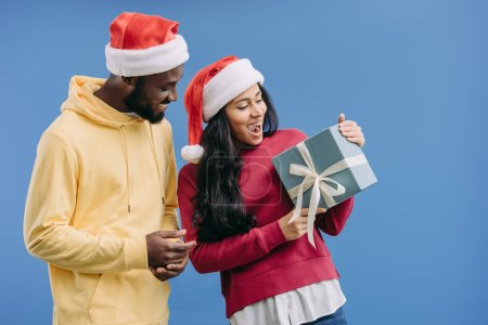 excited african american woman in christmas hat holding gift box while her boyfriend standing near isolated on blue background