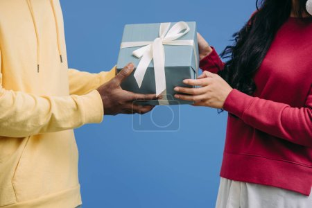 cropped image of man presenting gift box wrapped by ribbon to girlfriend isolated on blue background