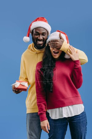 happy african american man in christmas hat holding gift box and closing eyes of girlfriend isolated on blue background
