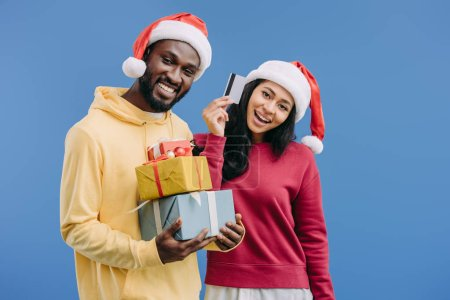 cheerful african american man in christmas hat holding gift boxes while his girlfriend showing credit card isolated on blue background