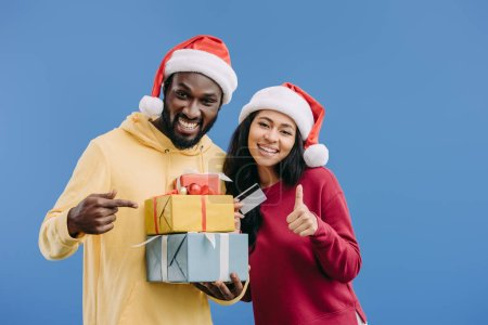 african american man in christmas hat pointing at gift boxes while his girlfriend holding credit card and doing thumb up gesture isolated on blue background