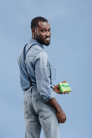 young african american man with gift box wrapped by ribbon looking at camera isolated on blue background