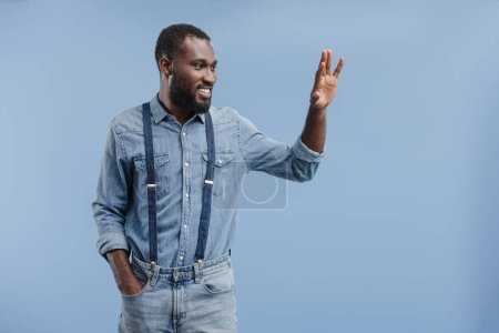 happy young african american man waving by hand isolated on blue background