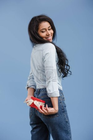 smiling attractive african american girl holding red gift box isolated on blue