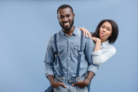 african american girlfriend hugging boyfriend and sticking tongue out isolated on blue