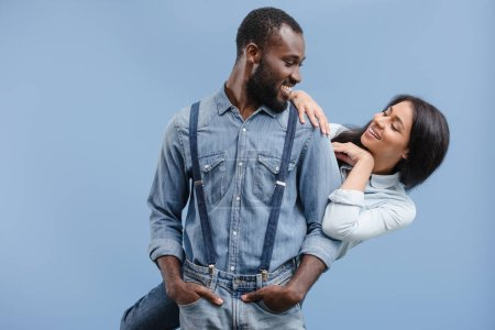 smiling african american couple hugging and looking at each other isolated on blue