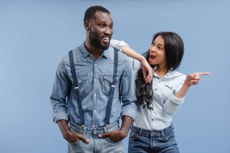 shocked african american girlfriend pointing on something to boyfriend isolated on blue