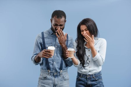 grimacing african american couple holding coffee to go and covering noses isolated on blue