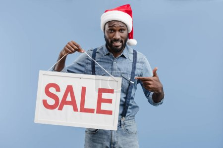 grimacing handsome african american man in santa hat pointing on sale sign isolated on blue