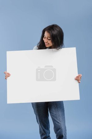 happy attractive african american girl looking at blank placard isolated on blue