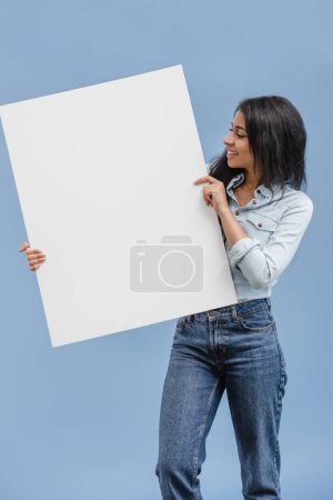 Photo for Smiling attractive african american girl looking at blank placard isolated on blue - Royalty Free Image