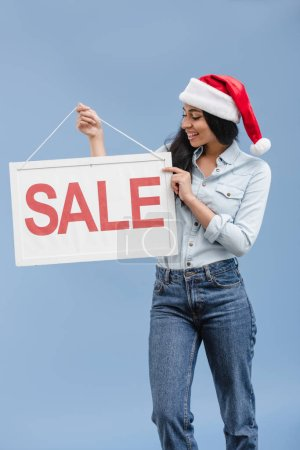 smiling attractive african american girl in santa hat looking at sale sign isolated on blue