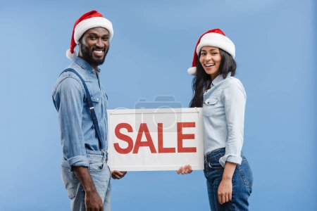 smiling african american couple in santa hats holding sale sign isolated on blue