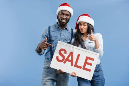 african american couple in santa hats pointing on sale sign isolated on blue