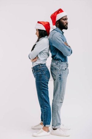 irritated african american couple in santa hats standing back to back with crossed arms isolated on white