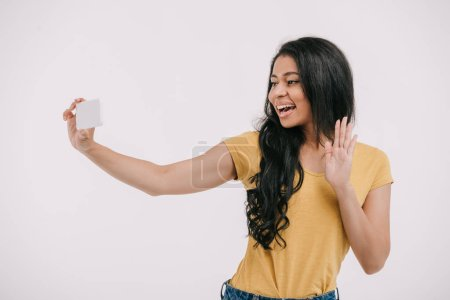 attractive african american girl waving hand during video call on smartphone isolated on white