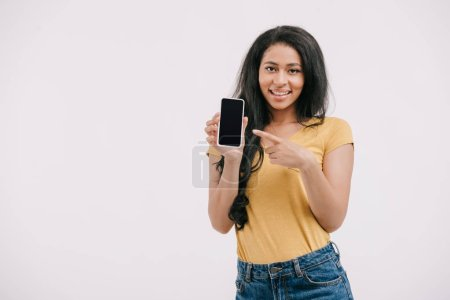 Photo for Smiling african american girl pointing on smartphone with blank screen isolated on white - Royalty Free Image