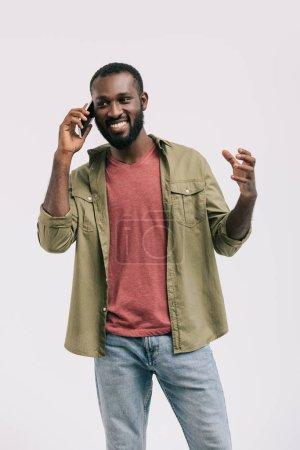 glücklich gutaussehender afrikanisch-amerikanischer Mann, der per Smartphone spricht und isoliert auf weißem Grund gestikuliert