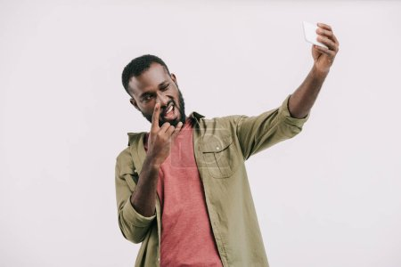 smiling handsome african american man taking selfie with smartphone and showing rock sign isolated on white