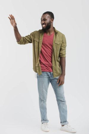 smiling handsome african american man waving hand and looking away isolated on white