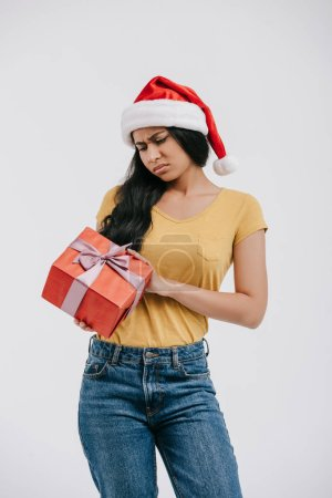 upset african american girl in santa hat holding present isolated on white