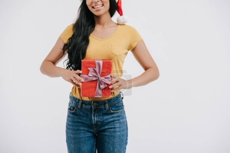 cropped image of smiling african american girl in santa hat holding present isolated on white