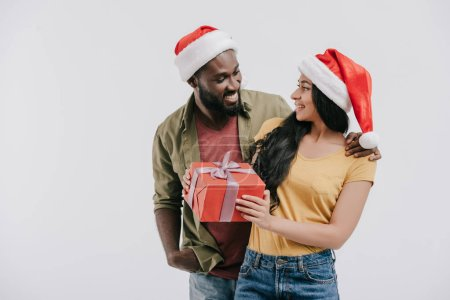 smiling african american couple in santa hats looking at each other and holding present isolated on white