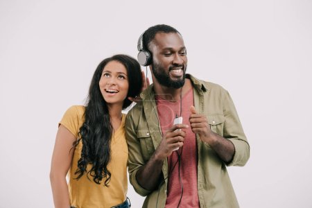 happy african american girlfriend eavesdropping boyfriend music isolated on white