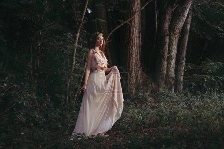 attractive mystic elf in elegant flower dress walking in woods