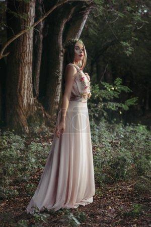 elegant mystic elf in flower dress posing in dark woods