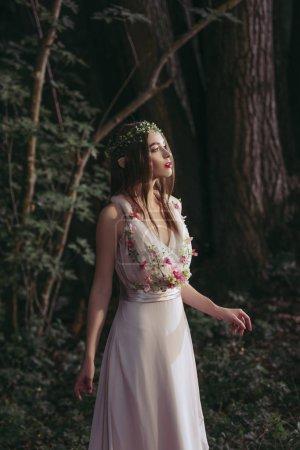 attractive mystic elf in dress with flowers in dark woods
